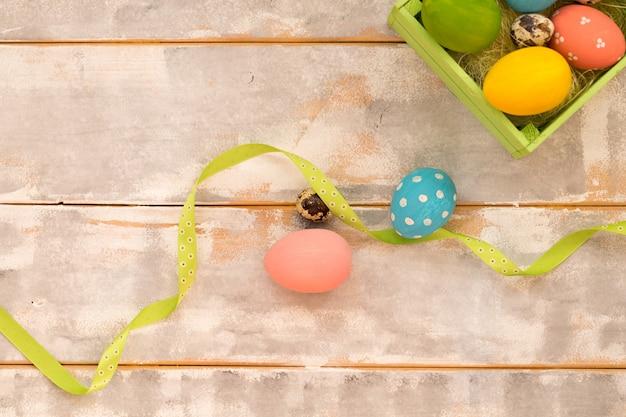 Разноцветные пасхальные яйца в деревянной коробке, ленты на дереве