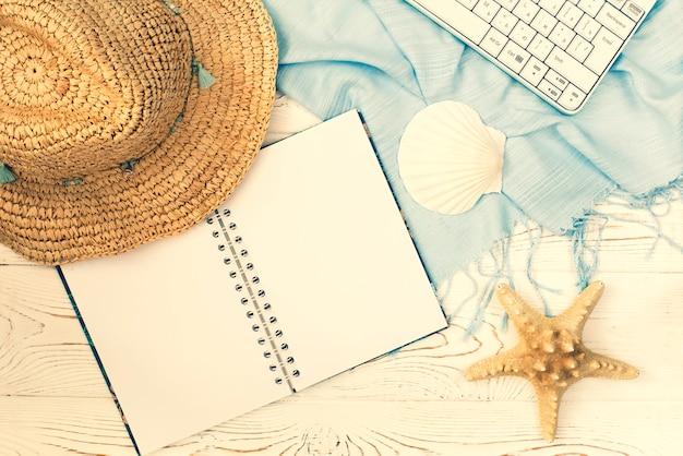 夏休みのノートと貝殻のフラットレイアウト
