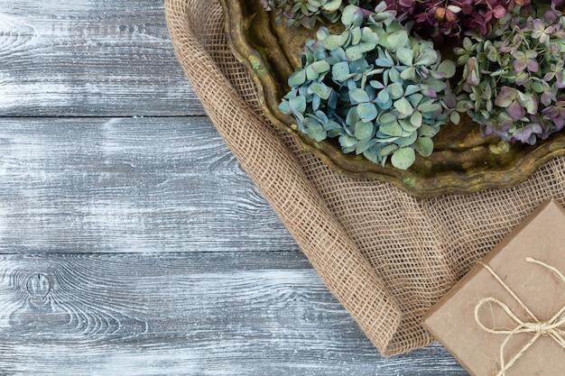 Винтажный поднос с высушенными голубыми цветками гортензий, подарочной коробкой обернутой в крафт-бумаге на мешковине на серой таблице. плоский стиль