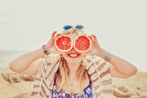 Радостная девушка с половиной грейпфрута.