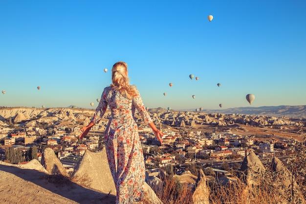 Женщина на рассвете наблюдая за воздушными шарами и наслаждаясь жизнью.