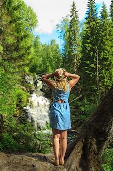 Женщина в шляпе, наслаждаясь природой возле лесного водопада.