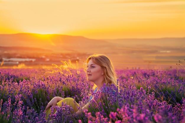 Девушка в сиреневом поле на закате. солнечный летний вечер в крыму.