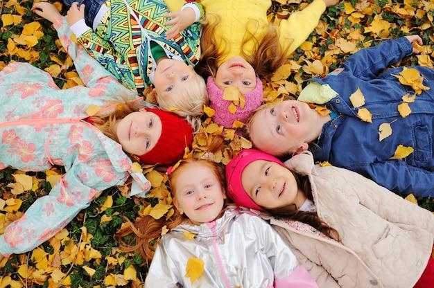 Группа детей лежит в осенних желтых опавших листьях в парке и улыбаются.