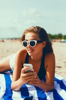 Девочка с очками и мобильный телефон в руке