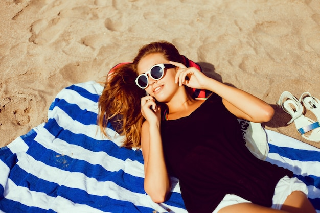 Девушка лежала на полотенце на пляже говорить на мобильный