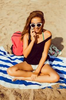 Девушка сидит на полотенце на пляже говорить на мобильный