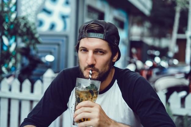 若い男は、カフェでスマートフォンを使用し、インターネットをサーフィンし、ビデオを見て、飲みます