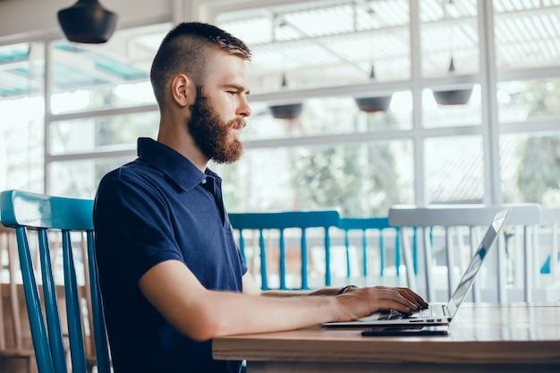 髭を持つ若い男はカフェで働き、フリーランサーはラップトップを使い、