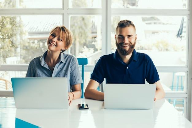 若いカップルは、プロジェクトをやっているカフェでラップトップで働いて、フリーランサーを与えます