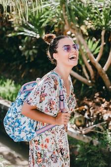 Молодая красивая девушка позирует на улице в платье с рюкзаком