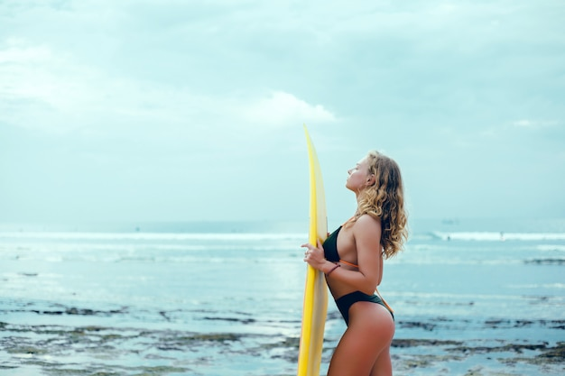 Молодая красивая девушка позирует на пляже с доской для серфинга, женщина-серфер, океанские волны