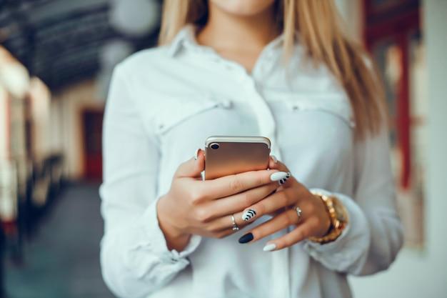 若い美しい女の子は、インターネットでサーフィン、通りにスマートフォンを使用して