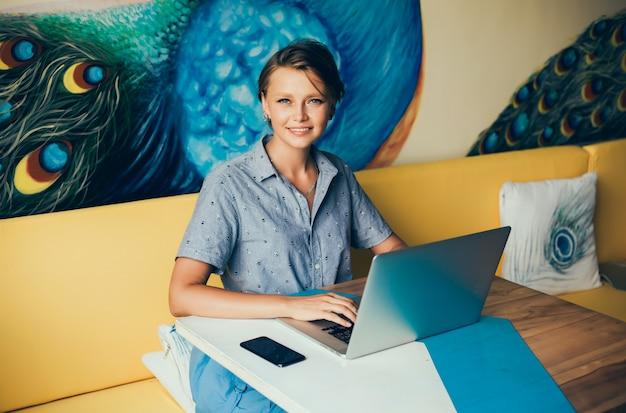 若い美しい女の子がカフェでラップトップを使用してインターネットをサーフィン