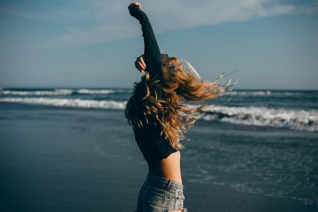 ビーチ、海、波、鮮やかな日差しと日焼けした肌でポーズを取る若い美しい少女