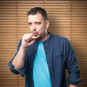 Молодой человек, одетый в синий наряд. кашляющий.