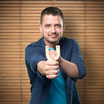 Молодой человек, одетый в синий наряд. с помощью рогатки. указывает на