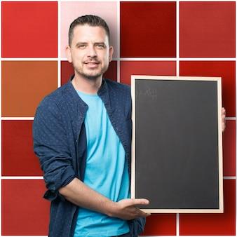 青い服を着ている若い男。黒板を保持しています。