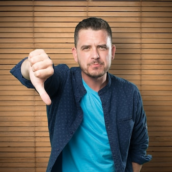 青い服を着ている若い男。ダウン親指で。