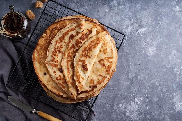 灰色の石のテーブルトップビューコピースペースにベリージャムと伝統的な自家製パンケーキを提供しています。