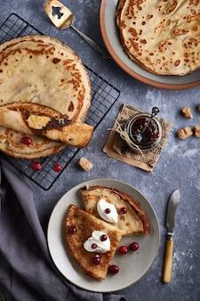 クランベリーと伝統的な自家製パンケーキは、灰色の石のテーブルで提供しています。上面図。