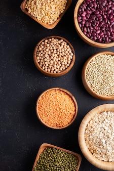 穀物、マメ科植物、穀物、穀物、レンズ豆、ひよこ豆、エンドウ豆、豆、木製ボウルのオートミールの品揃え