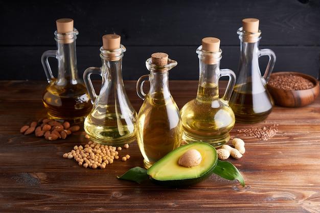 Полезные растительные масла в стеклянных бутылках. масло авокадо, масло нута, льняное масло, арахисовое масло, миндальное масло.