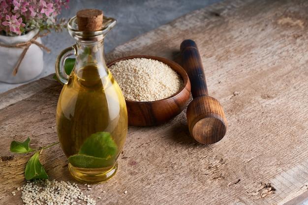 Здоровое кунжутное масло в стеклянной бутылке и семена кунжута на деревянном столе копирование пространства деревенский