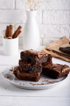 ブラウニーケーキの白いテーブルで提供していますチョコレートケーキ