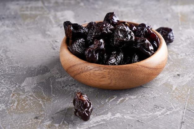 Чернослив, чернослив в деревянной миске на сером столе в деревенском стиле