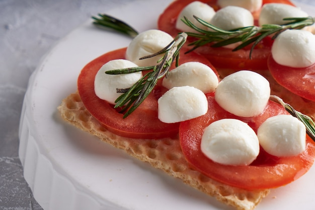 白い皿にモッツァレラチーズ、トマト、ローズマリーのトースト