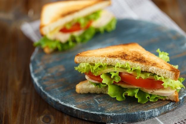 Два вкусных бутерброда с курицей, помидорами, листьями салата, сыром на деревянной тарелке на темном фоне