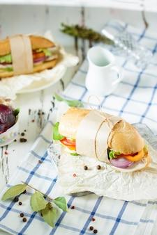 ダイニングテーブル。鶏肉、トマト、レタス、チーズ、スパイス入りのシャキッとしたパンのサンドイッチ。