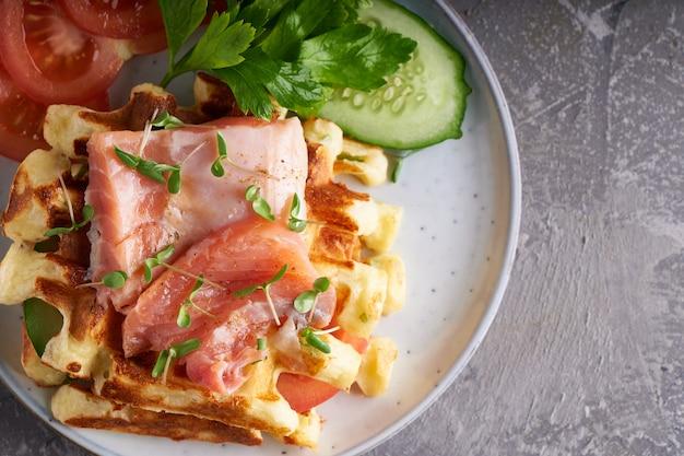 Домашние вафли с лососем, огурцом и зеленью на тарелке