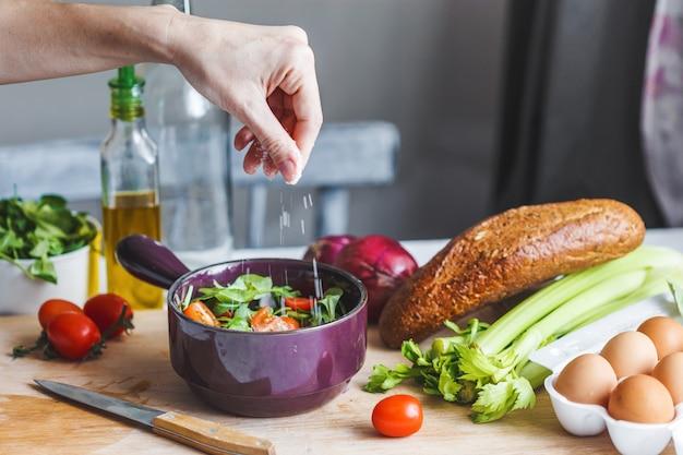 シェフの手がキッチンで新鮮でヘルシーな食材、野菜、オリーブオイルのサラダを準備します。