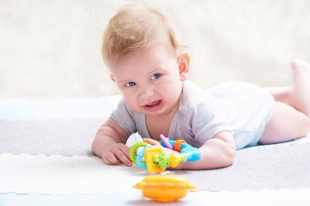 Милый плачущий малыш с игрушками