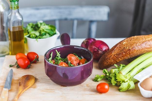 新鮮な野菜サラダと台所のテーブルで調理するための食材のボウル