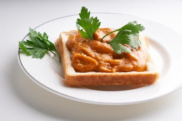 ズッキーニキャビアと健康的なトースト。白いテーブルの上のハーブとプレートでお召し上がりいただけますロシアの伝統的なサンドイッチ