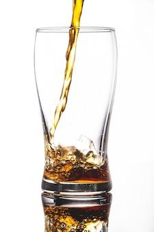 Лить колу в стакан со льдом на белом