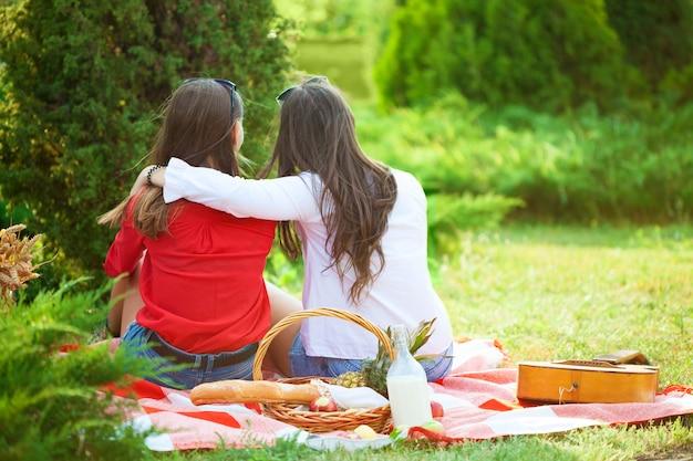 Две красивые молодые девушки на пикнике летом в парке веселиться и разговаривать