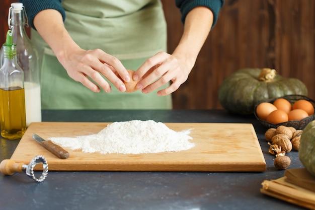 女性の手が生地をこねます。菓子職人は卵を小麦粉に打ち込んでいます。木製のテーブルには食材を焼きます。