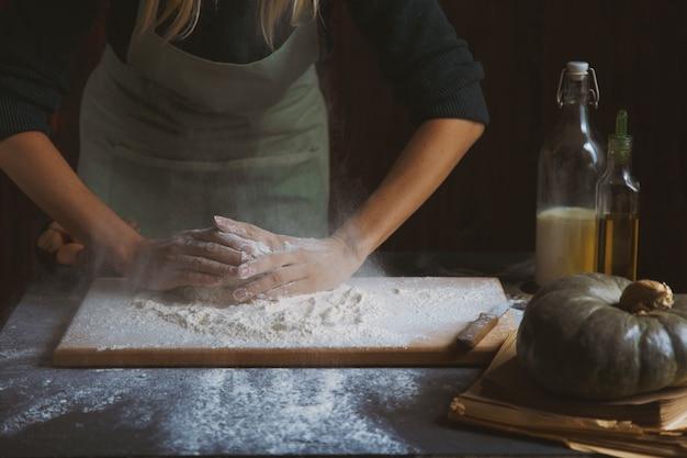 女性の手が生地をこねます。木製のテーブルに食材を焼く
