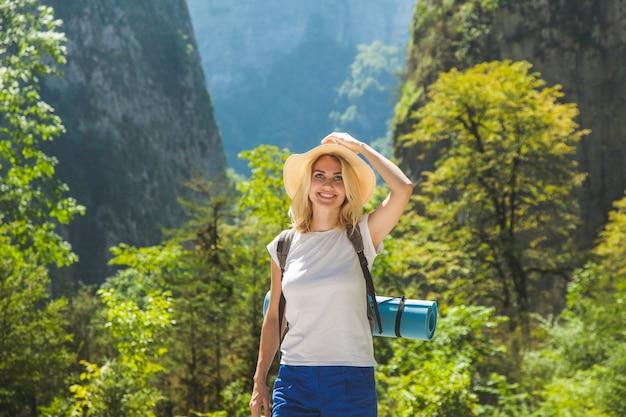 帽子をかぶった流行に敏感な女の子が山を旅します女の子は旅行が大好きです。背景の山に観光旅行者の後ろからの眺め