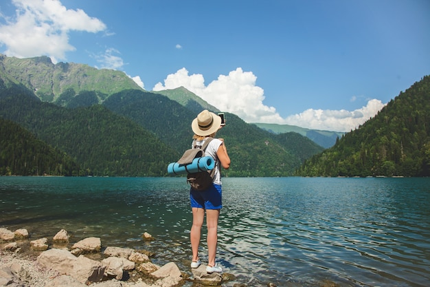 帽子の美しい少女旅行者は山の背景に湖の上に立つ