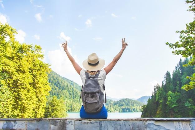 美しい少女旅行者は山の背景に大きな青い山の湖に座っています。彼女は彼女の手を振る