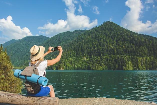Красивая девушка-путешественница фотографирует большое голубое горное озеро на фоне гор