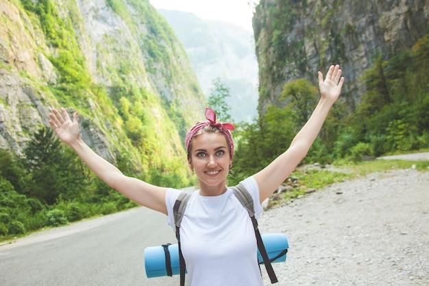 Девушка-путешественница в горах машет руками и смеется