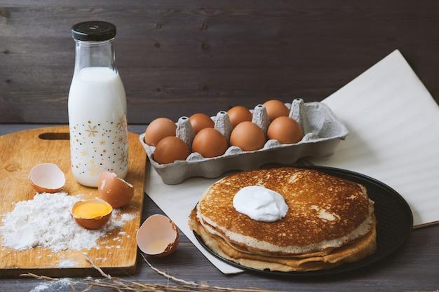 フライパン、卵、牛乳、木製のテーブルの上に小麦粉で新鮮な熱いパンケーキ。
