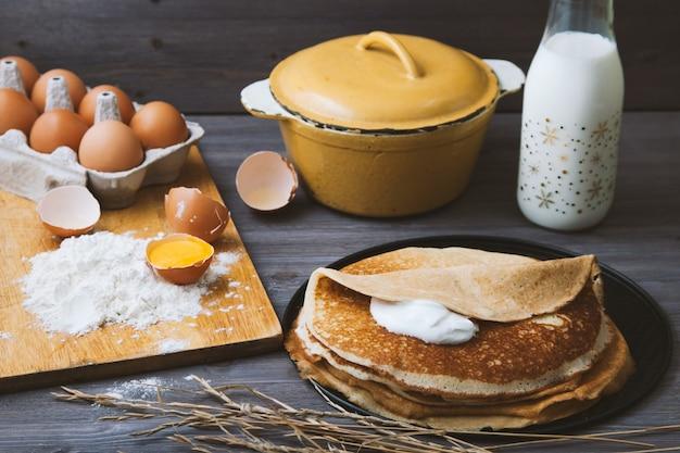 フライパン、卵、牛乳、木製のテーブルの上に小麦粉で新鮮な熱いパンケーキ。上面図