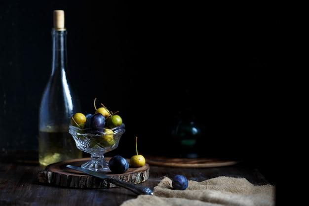 Дикая груша и слива в стеклянной миске и бутылка домашнего груши вина